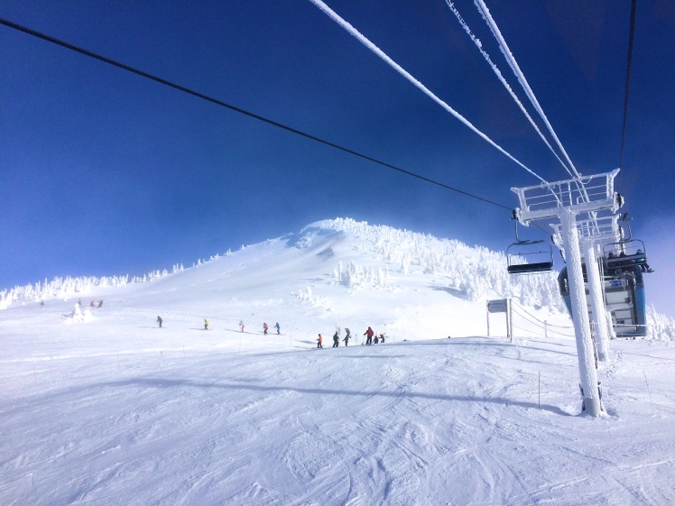 Clear blue skies and snow-covered chairlift at Revelstoke, B.C. Perfect ski/snowboard day.